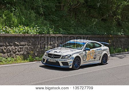 PASSO DELLA FUTA (FI) ITALY - MAY 21: driver and co-driver on a racing car Mercedes-Benz C63 AMG (2012) in italian historical race Mille Miglia on May 21 2016 in Passo della Futa (FI) Italy