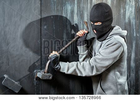 a burglar breaking open of a padlock metal door