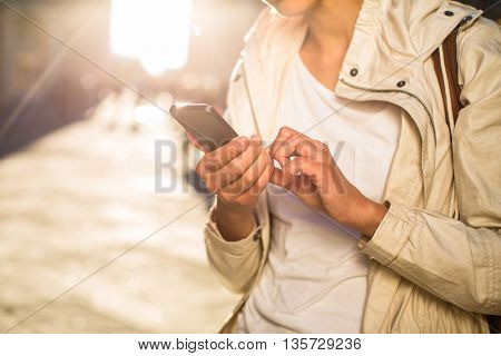 Young woman messaging/using app on her smart-phone in a city street context (shallow DOF; color toned image)