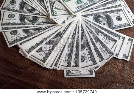 Many 100 dollar bills. Money on wooden table background