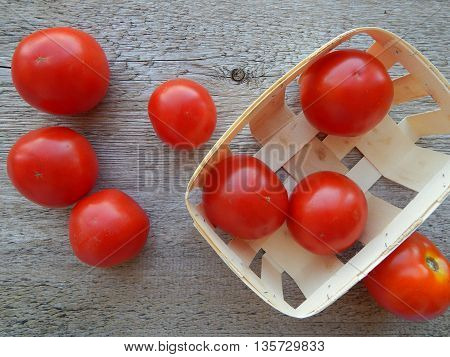 Portrait of spilled tomatoes from rattan basket on wood background