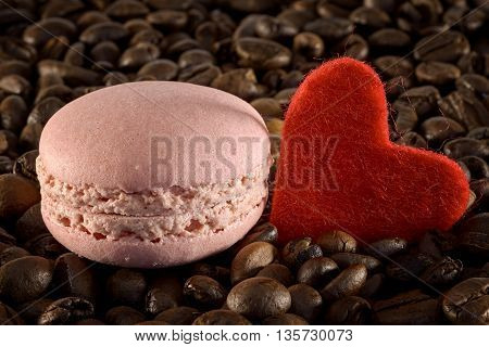 pink macaron and red heart on coffee beans
