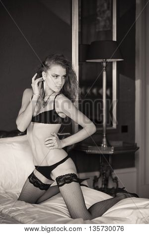 Woman in erotic black underwear in bedroom