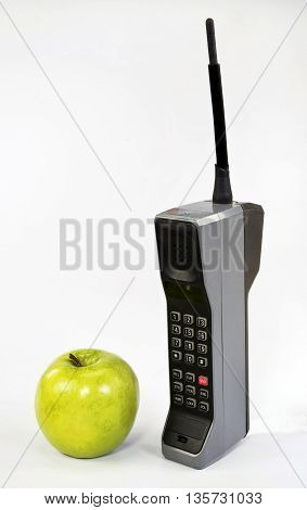 Green apple and old brick style cell phone.