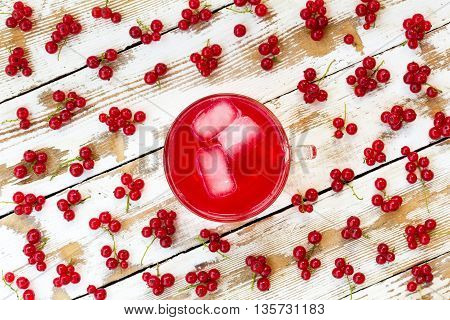 freshly squeezed red juice with ice cubes and bunches of red currants on a white wooden table with old paint. closeup flat lay