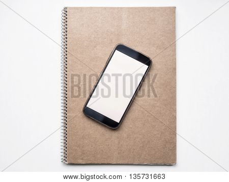 Mockup of Modern smartphone with white blank screen on kraft notebook cover