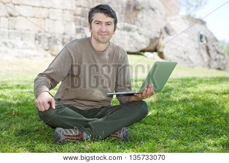 man sitting on the grass working on a laptop