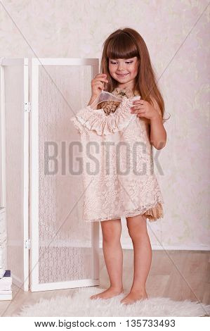 a little girl tries on a dress