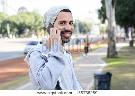 Portrait of young latin man talking on the phone. Outdoors.