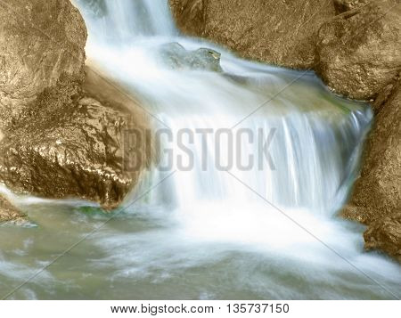 Beautiful waterfall and gold rocks around it