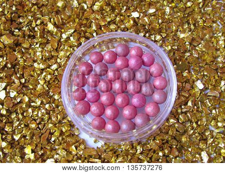 Pink blush on gold background made of little gold rocks