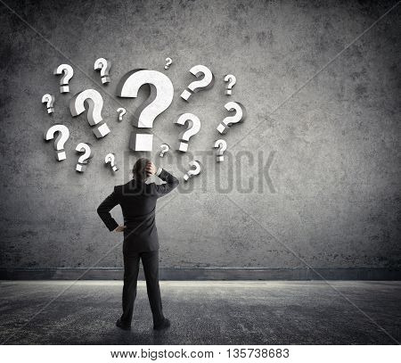 Thoughtful businessman with questions marks around the head