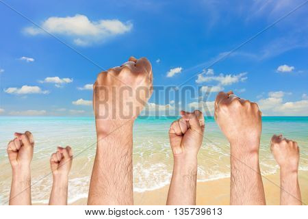 Human hands showing fist on blue sky background.