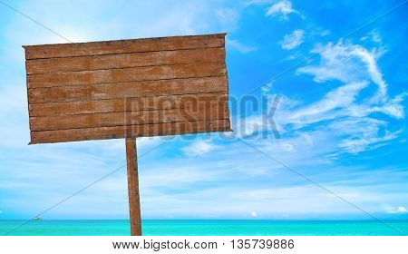 wooden signboard with blurred beach with blue sky background on sunny day.