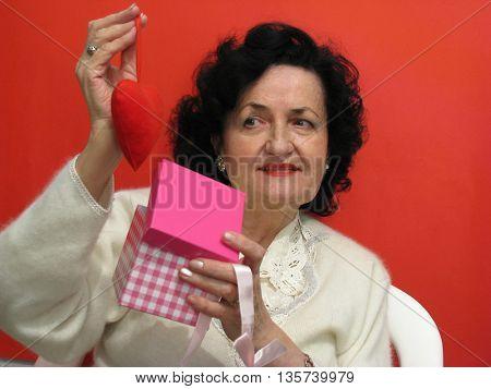 Beautiful mature woman holding a gift box and heart