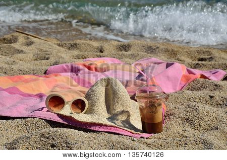 Coffee frappe pink-orange towel hat and sun glasses on the beach by the sea