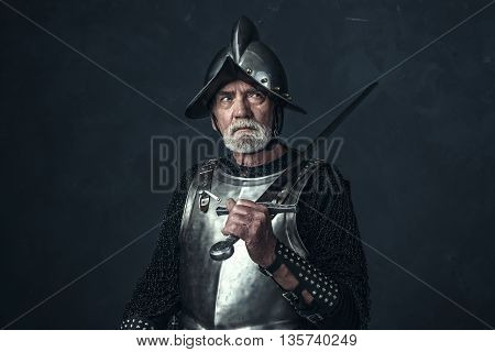 Knight In Armor With Gray Beard Holding Sword.