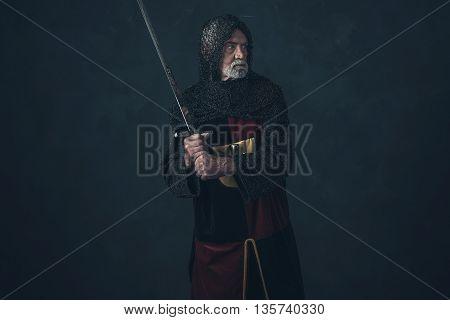 Senior knight in hauberk attacking with sword.