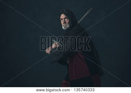 Senior knight in hauberk attacking with sword.