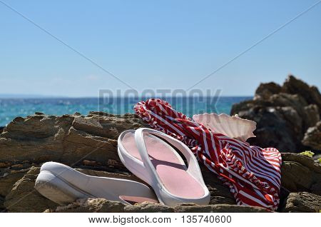Swimsuit and flip flops left on the rocks by the sea