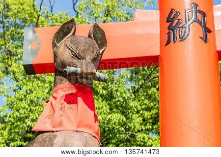 Kyoto, Japan - Circa May 2016: Fushimi Inari Stone Fox Guarda Wooden Gates. Foxes Are Believed To Be