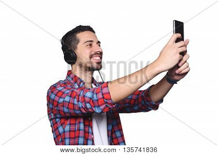 Portrait of attractive young man taking a selfie with his smartphone and black headphones. Isolated white background.