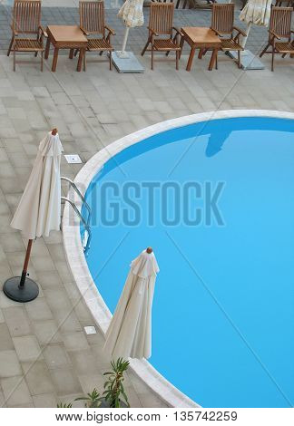beautiful swimming pool surrounded by chairs and sun umbrella