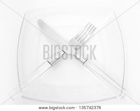 Dinner place setting. A glass china plate with silver fork and knife isolated on white background.