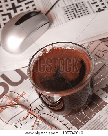 Coffee cup and computer mouse with glasses on news