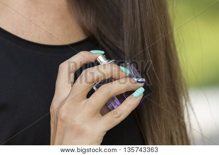 Arm girls with beautiful manicure holding purple bottle with spirits