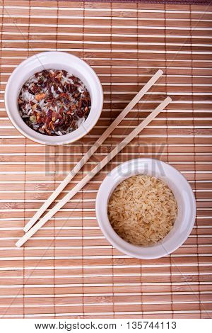 Bowls with raw rice and chopsticks on the bamboo tablecloth