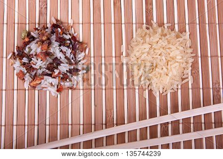 Raw rice with spices and chopsticks on the bamboo tablecloth