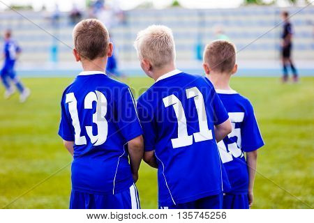 Young soccer team. Reserve players standing together and watching football soccer tournament match for youth teams. Sports background.