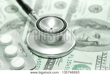 health care costs - Stethoscope on money background and pills
