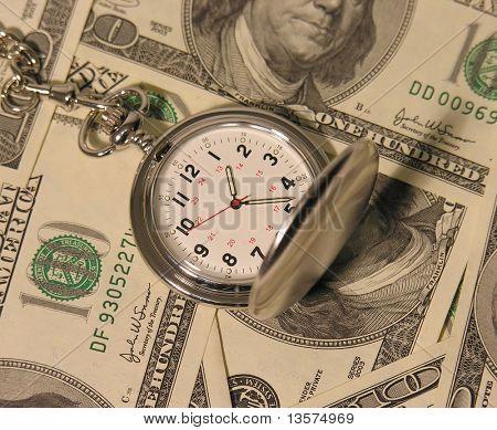 Uma foto de um relógio de bolso em cem notas de dólar