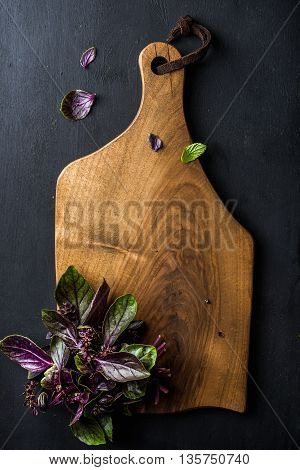 Violet basil bunch on wooden chopping board over black background, top view, copy space