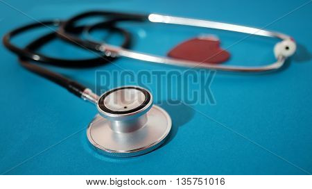stethoscope and shape of heart isolated on blue background