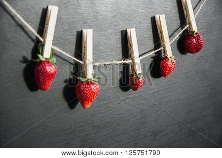 drying berries on a wooden clothespin black background