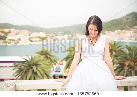 Beautiful woman enjoying the sea view from the balcony.Perfect view.Enjoying summer holiday.Perfect holiday concept.