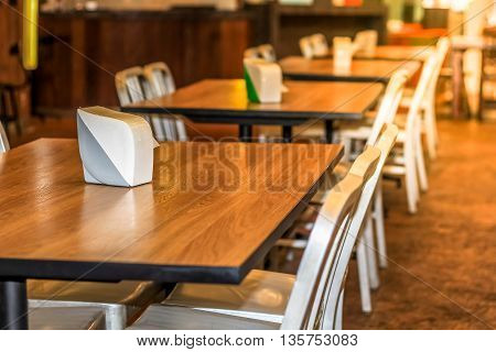 Set of dining table Wood table top and white chairs in the hotel restaurant decorate with warm light