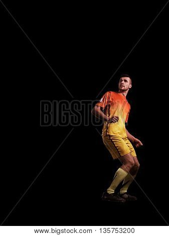 Strong and young soccer player in action on black background