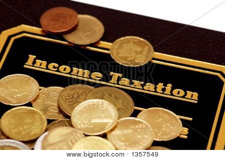 "Book Of ""Income Taxation"" And Coins Isolated On White"