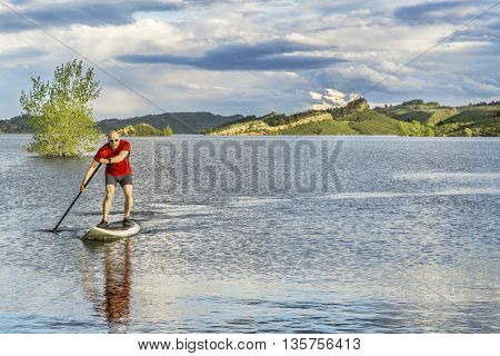 mountain lake landscape with a senior male paddling a SUP paddleboard with a copy space - Horsetooth Reservoir, Fort Collins, Colorado