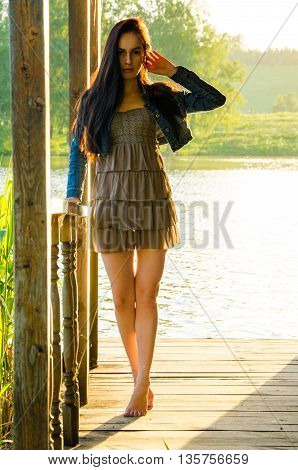 girl standing on a wooden pier . barefoot brunette in a short summer dress . It is standing on tiptoes . on the pier at the pond. Brunette walks barefoot on the wooden floor near the lake