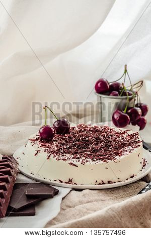 Light vanilla no bake bavarian mousse cake with ripe cherries and dark chocolate. White plate. No-bake summer dessert.