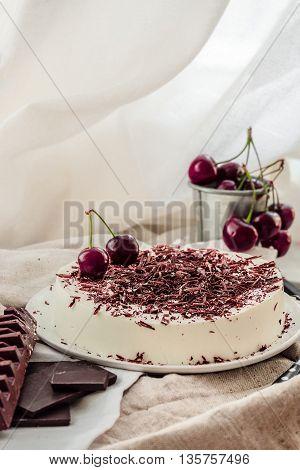 Light vanilla no bake bavarian mousse cake with ripe cherries and dark chocolate. White plate. No-bake summer dessert.