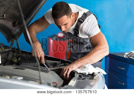 Worthy auto mechanic in a workshop, close up