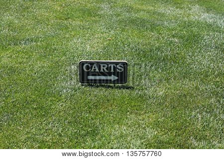 This is an image of a cart directional sign on a golf course fairway.