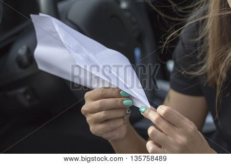 Paper plane in the hands of a girl with beautiful manicure sitting in the car.