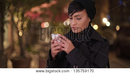 Fashionable Woman In Black Overcoat On Urban City Street At Night Making Phone Call On Cellphone
